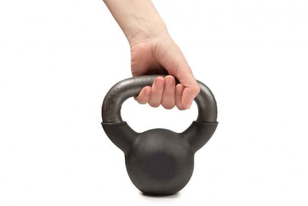 Czarny ciężar odizolowywający na bielu w kobiety ręce. waga 4 kg.
