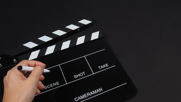 Czarny clapperboard lub clap board lub łupek filmowy z ręką trzymającą pióro w produkcji wideo, filmie, przemyśle kinowym na czarnym tle.