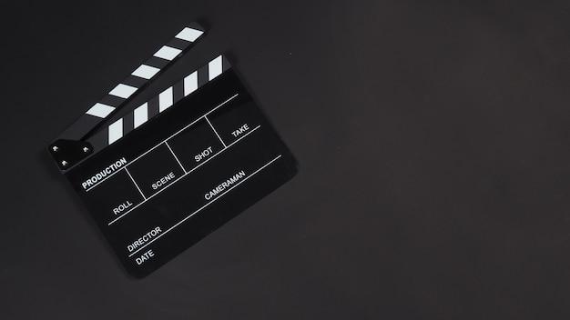 Czarny clapperboard lub clapboard lub plansz filmowy do produkcji wideo, filmu, przemysłu kinowego na czarnym tle.