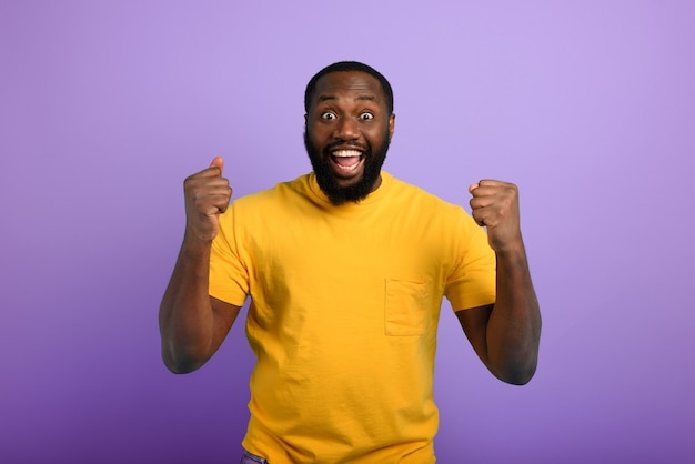 Czarny człowiek jest szczęśliwy. wyraz radości i szczęścia. fioletowe tło