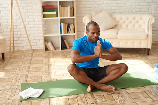 Czarny człowiek medytuje w pozycji lotosu na macie w domu.