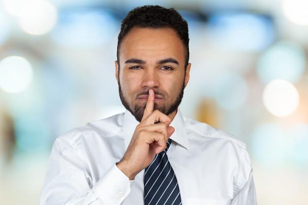 Czarny człowiek pokazuje ciszy gest z palcem na ustach