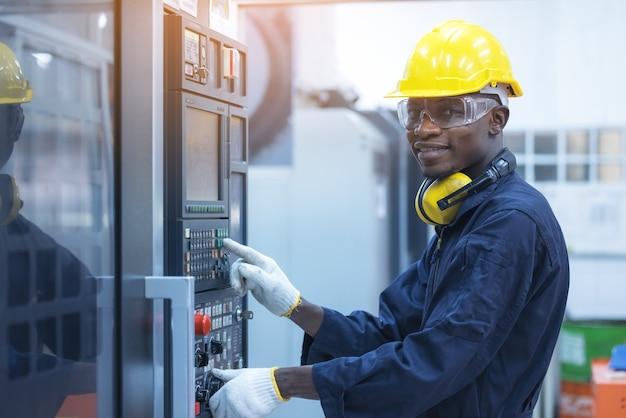 Czarny człowiek pracujący na programowalnej maszynie w fabrykach