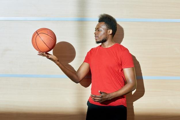 Czarny człowiek przędzenia piłkę na palcach