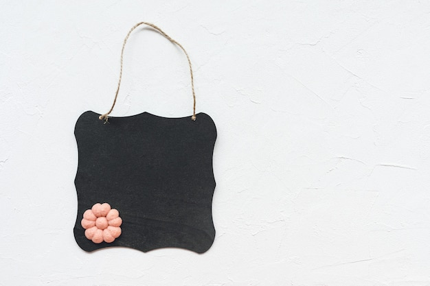 Czarny deski i kwiatu ciastko na bielu
