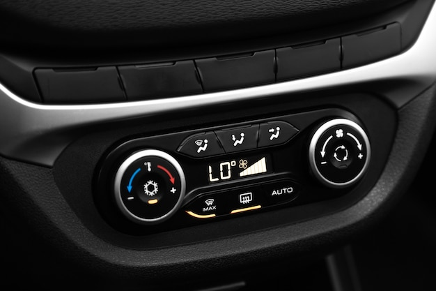 Czarny detal z przyciskiem klimatyzacji, deska rozdzielcza z informacją o temperaturze wewnątrz auta.