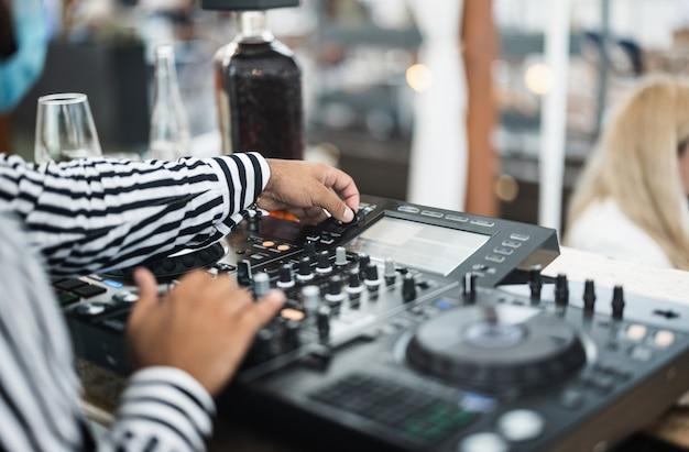 Czarny dj grający muzykę w koktajl barze na świeżym powietrzu, mając na sobie maskę ochronną na twarz - rozrywka, dystans społeczny i koncepcja imprezy - skoncentruj się na lewej ręce