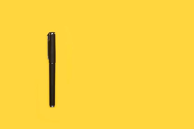 Czarny długopis na żółtym tle z miejsca na kopię
