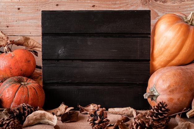 Czarny drewniany znak z stos dyni i szyszki