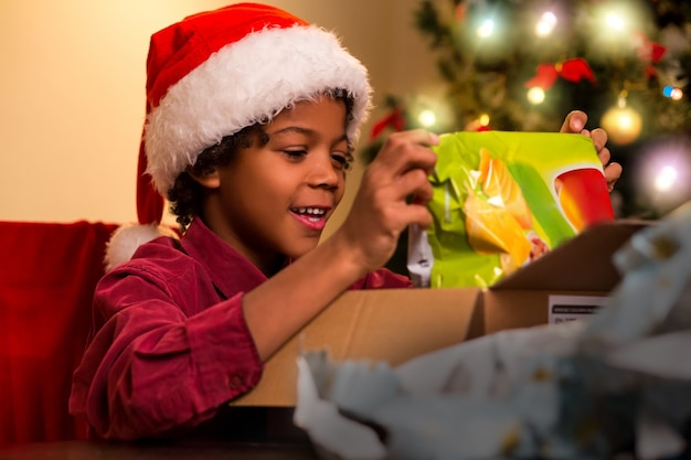 Czarny dzieciak otwierając świąteczny prezent.