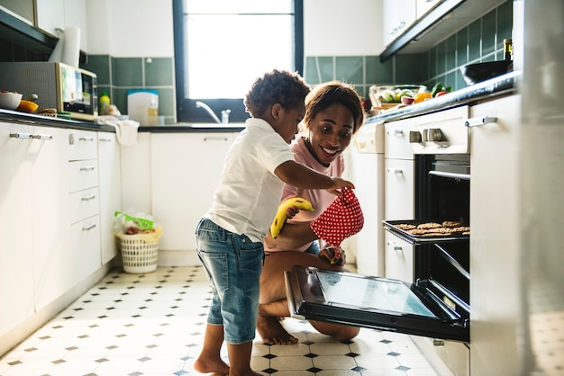 Czarny dzieciak pomaga mama wypiekowi ciastka