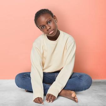 Czarny dzieciak w beżowym swetrze