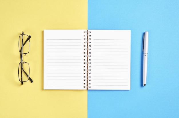 Czarny ekran notebooka puste i pióro umieszczone na pastelowy żółty