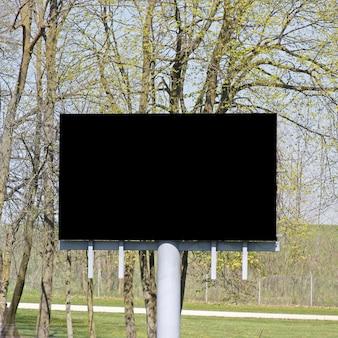 Czarny ekran tv billboard z gałęziami drzew