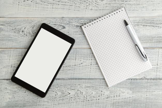 Czarny elektroniczny pastylki i papieru notatnik na rocznika podławym białym drewnie, odgórny widok