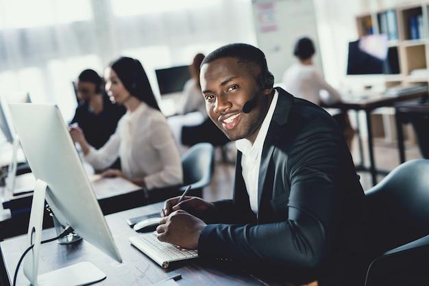 Czarny facet pracuje w call center z ludźmi.