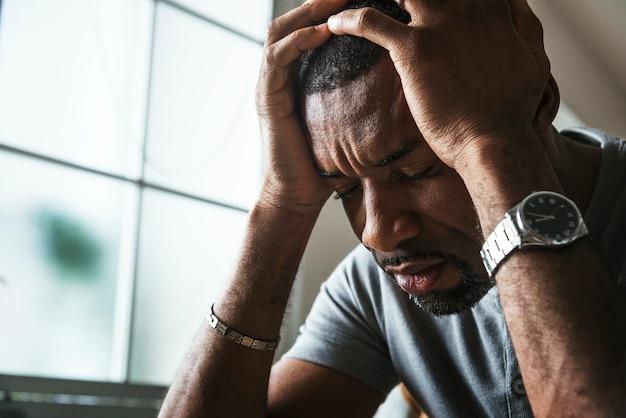 Czarny facet stresujący i ból głowy