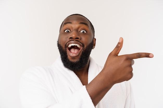 Czarny facet w szlafroku, wskazując palcem z zaskoczenia i szczęśliwy emocji. pojedynczo ponad whtie.