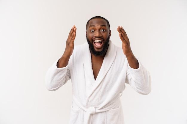 Czarny facet w szlafroku, wskazując palcem z zaskoczenia i szczęśliwy emocji.