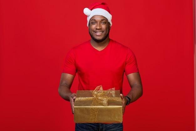 Czarny facet z uśmiechem zębów w czapce mikołaja daje prezent na boże narodzenie na czerwonym tle