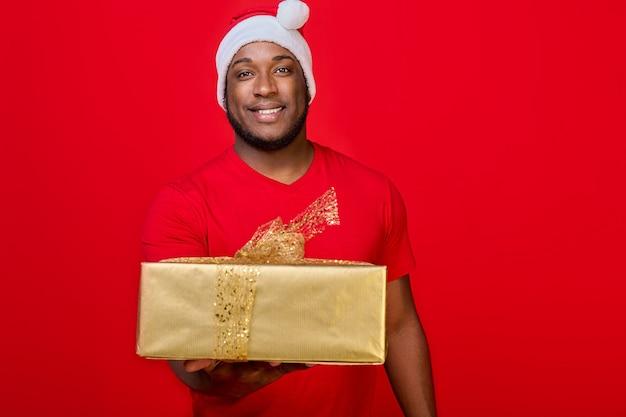 Czarny facet z uśmiechem zębów w czapce mikołaja daje prezent świąteczny w złotym opakowaniu