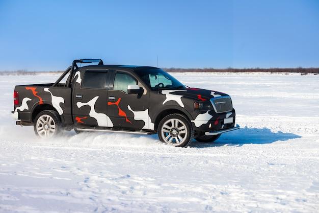 Czarny ford f-150 szybko poruszający się po śniegu