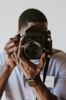 Czarny fotograf robiący zdjęcie aparatem na kliszę retro