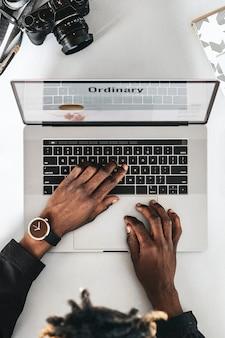 Czarny fotograf używający laptopa