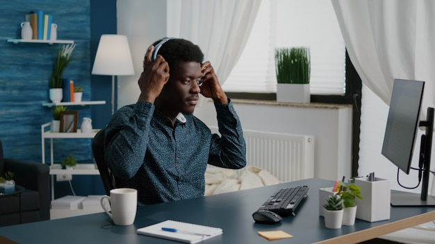Czarny freelancer o afrykańskim pochodzeniu, zakładający słuchawki podczas pracy w domu zdalna kooper...