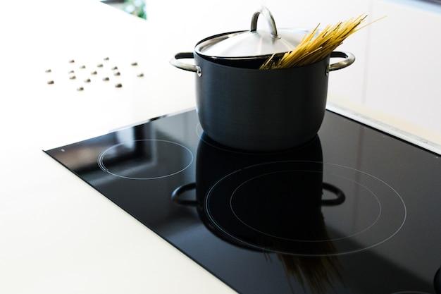 Czarny garnek z pokrywką do gotowania spaghetti w nowoczesnej kuchni na płycie indukcyjnej. indukcyjna kuchenka elektryczna