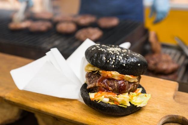 Czarny hamburger i biała papierowa serwetka na drewnianej desce do krojenia, japońska specjalność kulinarna z dodatkami w postaci bambusowego węgla drzewnego i atramentu kałamarnicy, zbliżenie