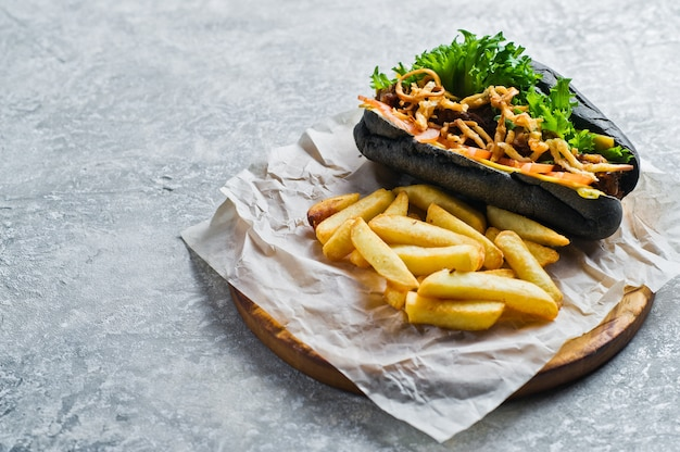 Czarny hot dog z kebabem wołowym i karmelizowaną cebulą.