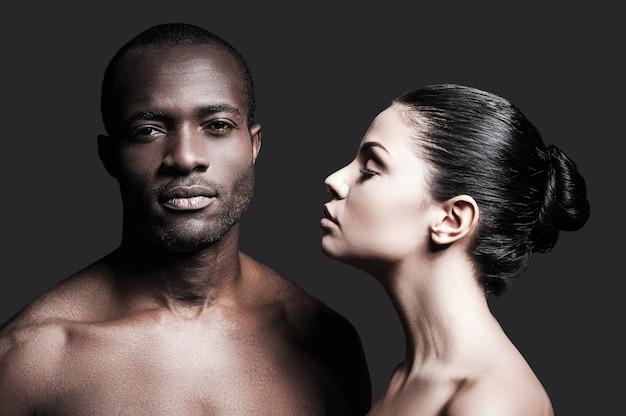 Czarny i biały. portret bez koszuli afrykańskiego mężczyzny i kaukaskiej kobiety, którzy łączą się ze sobą, stojąc na szarym tle
