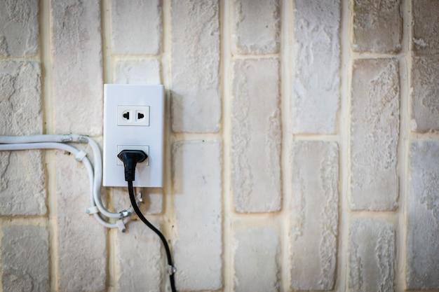 Czarny kabel zasilający podłączony do gniazda ściennego na białym tynku ceglanym murem z miejscem na kopię.
