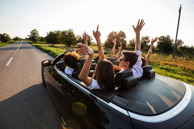 Czarny kabriolet jest na wiejskiej drodze. szczęśliwa grupa młodych dziewcząt i chłopaków siedzą w samochodzie, trzymając ręce w słoneczny dzień. .