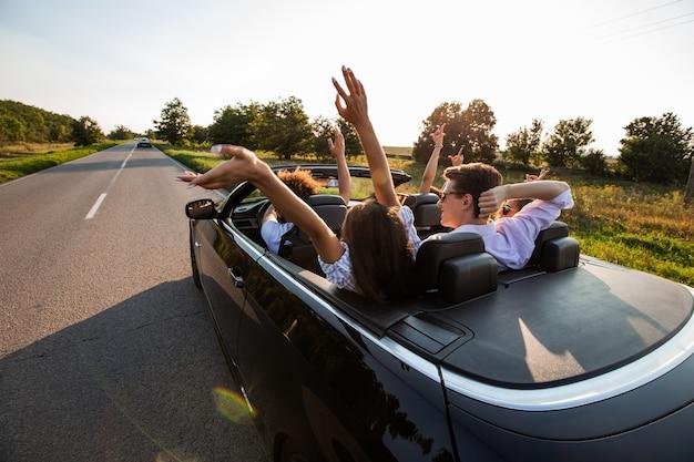 Czarny kabriolet jest na wiejskiej drodze. towarzystwo młodych dziewcząt i chłopaków siedzi w samochodzie trzymając ręce do góry w słoneczny dzień. .
