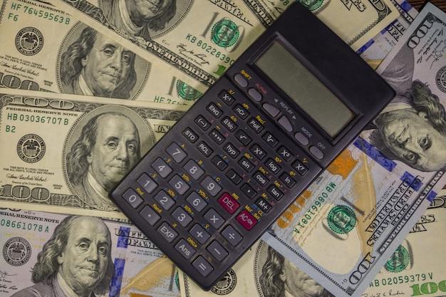 Czarny kalkulator na tle amerykańskich banknotów studolarowych