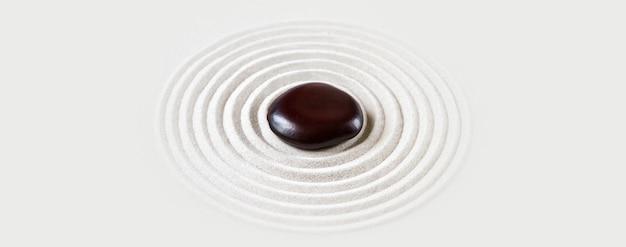 Czarny kamień w piasku zen japoński ogród tło sceny poziomy baner