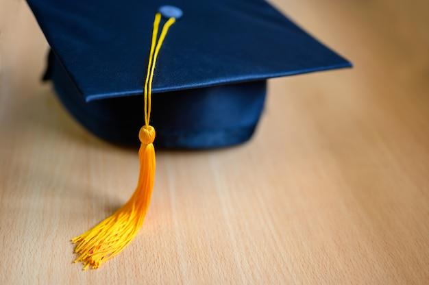Czarny kapelusz absolwentów leżał na drewnianej podłodze.