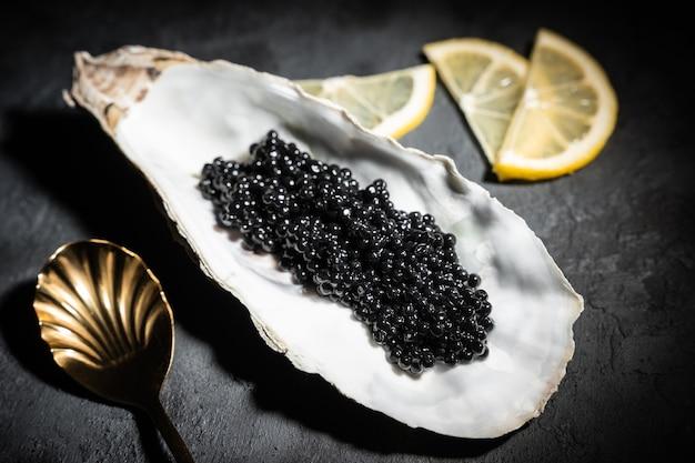 Czarny kawior w muszli ostryg na czarnym tle łupków