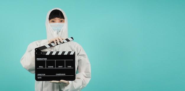 Czarny klaps lub łupek filmowy. azjatycka kobieta nosić maskę i garnitur ppe na miętowym zielonym lub tiffany blue tle.