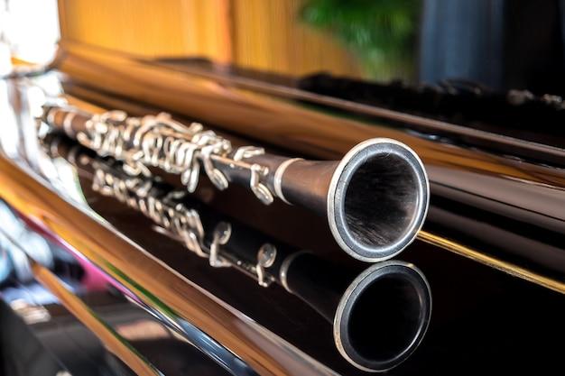Czarny klarnet leżący na fortepianie zamykania