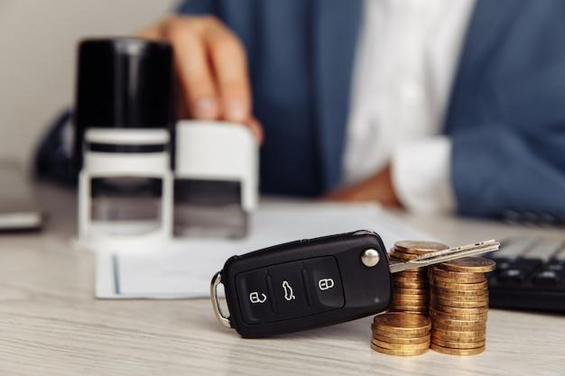 Czarny kluczyk i pieczęć na podpisanej umowie sprzedaży samochodu.