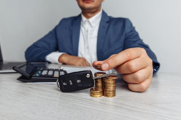 Czarny kluczyk z umową na drewnianym stole i człowiek z pieniędzmi. koncepcja biznesowa, finanse i ubezpieczenia, plany oszczędnościowe dla samochodu