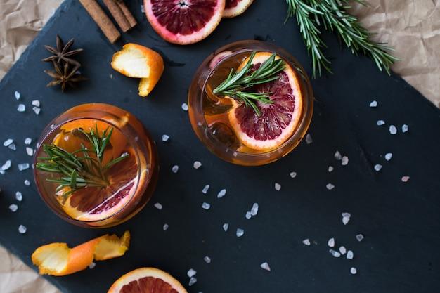Czarny koktajl negroni podany z plasterkiem pomarańczy i rozmarynu.