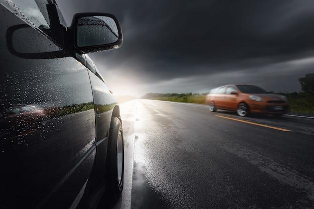 Czarny kompaktowy samochód suv z chmurami sztormowymi, transport w złych warunkach pogodowych.