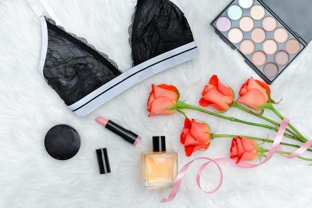 Czarny koronkowy stanik na białym futrze. pomarańczowe róże, szminka, perfumy i cień do powiek