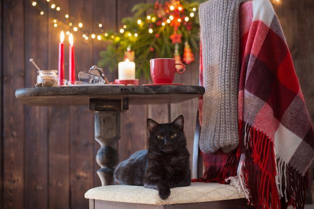 Czarny kot na krześle z drewnianym stołem z świąteczną dekoracją