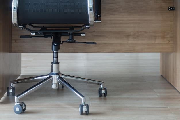 Czarny krzesło obrotowe pod stół biurowy na drewnianej podłodze.