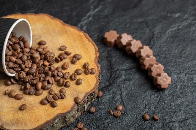 Czarny kubek pełen ziaren kawy na desce.